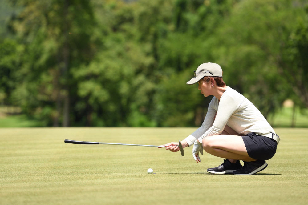 Woman golfer relaxing on course