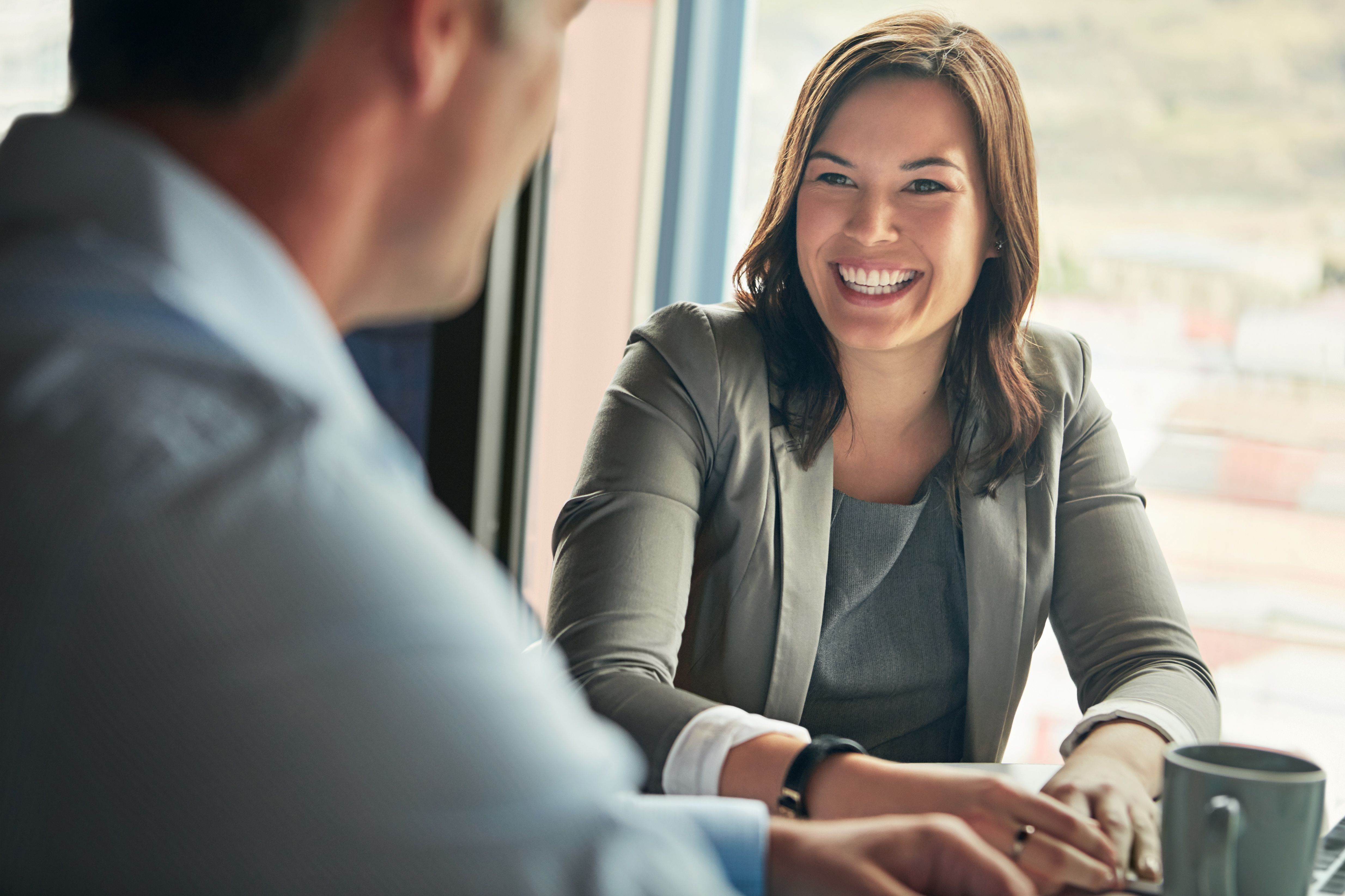 Shot of two businesspeople talking together while sitting a table in an office